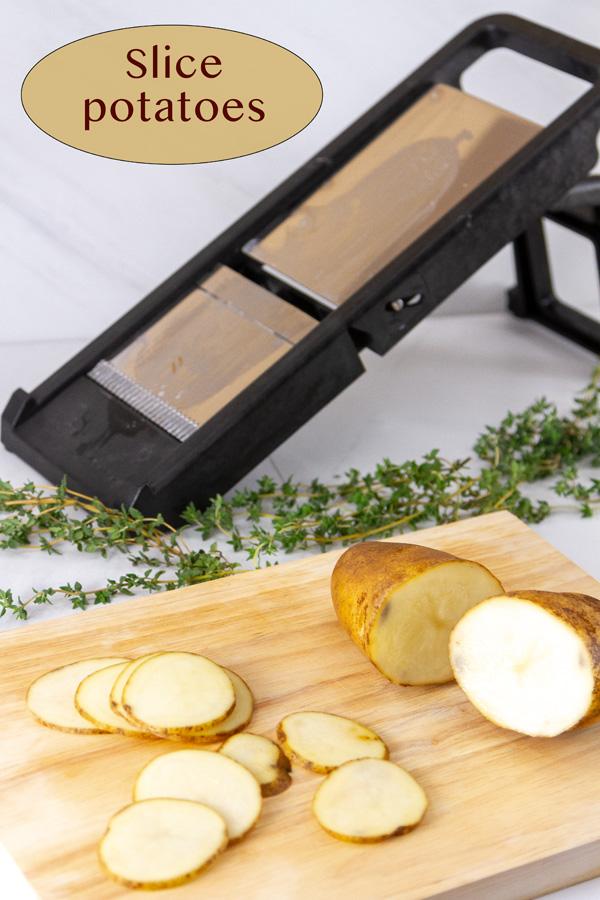 a mandoline, sliced potatoes, and a potato cut in half on a cutting board.