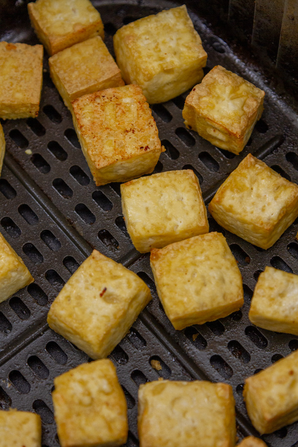 cooked tofu in an air fryer basket