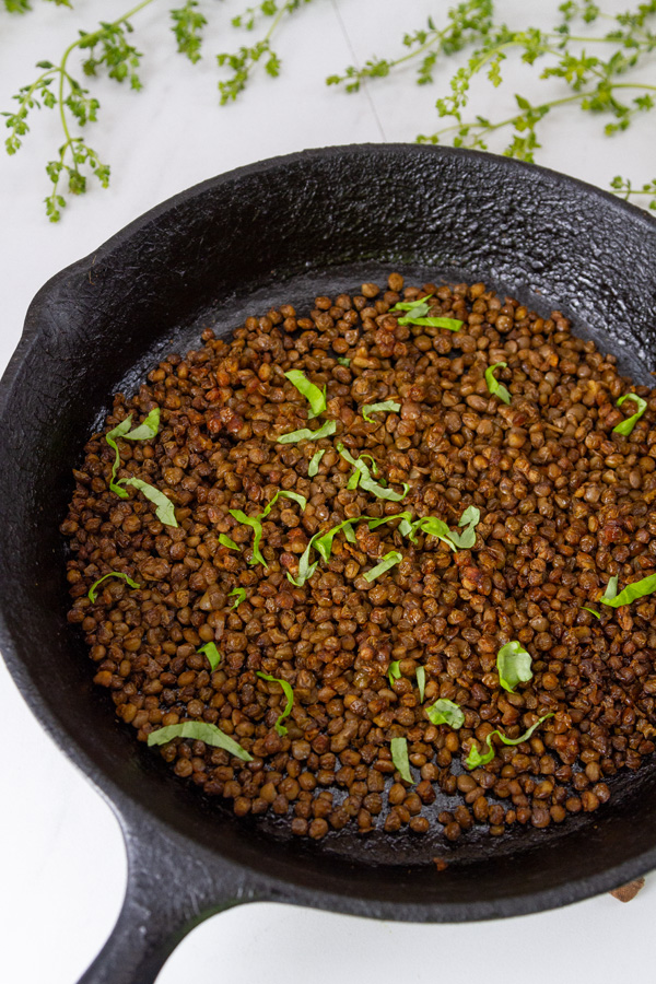 cooked lentils in a cast iron skillet garnished with chopped basil.