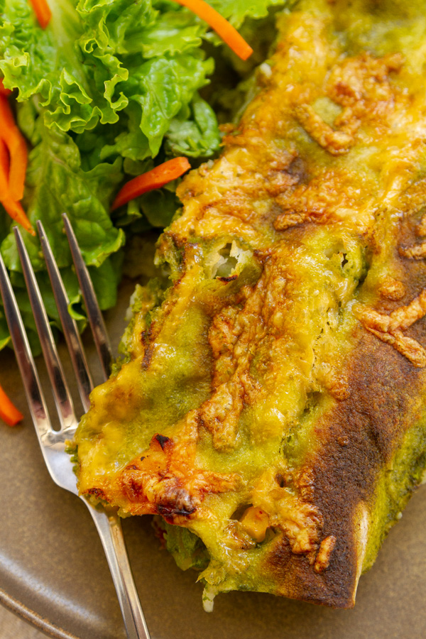 top down view of green enchiladas with a fork and a salad.