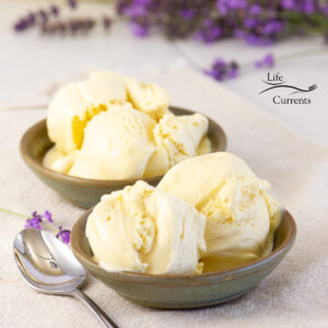 square crop of two bowls of ice cream with a spoon and lavender flowers.