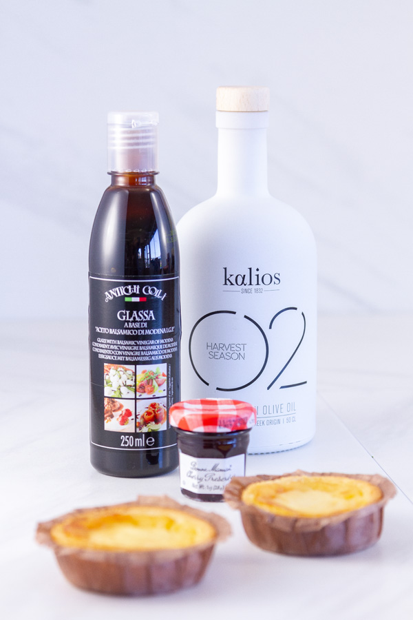 a bottle of olive oil, balsamic glaze, cherry preserves, and two custard tarts.