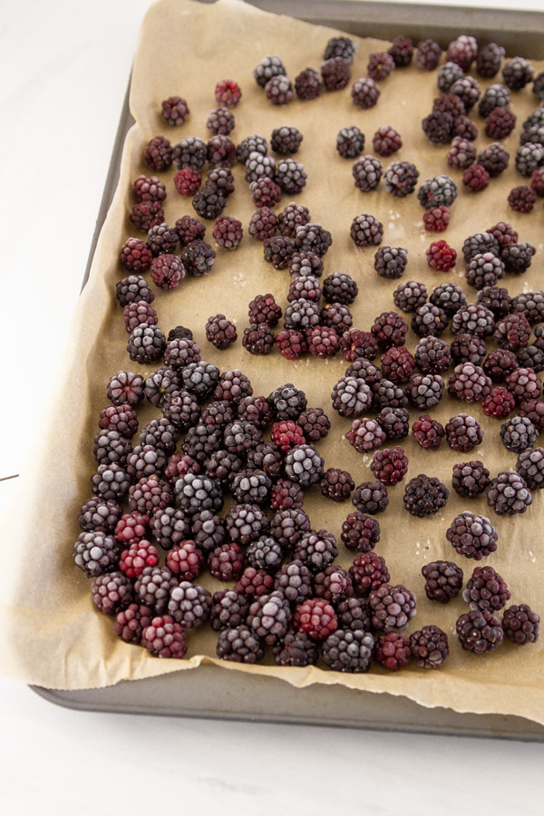 frozen blackberries on a parchment paper lined baking tray.