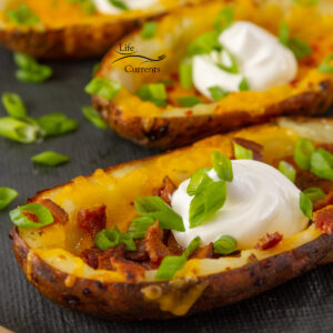 square crop of potato skins filled with cheese, bacon, green onions, and sour cream.