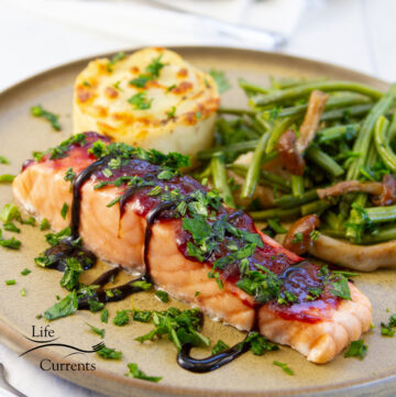 square crop of a roasted salmon with cherry preserves and balsamic served with potatoes and green beans.