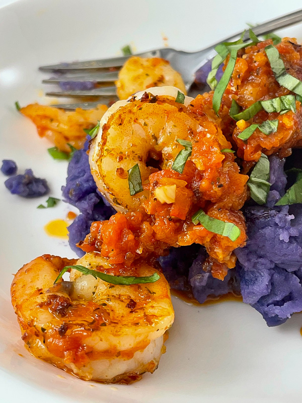 seared shrimp in red pepper sauce on mashed purple potatoes garnished with fresh basil, a fork in the background.