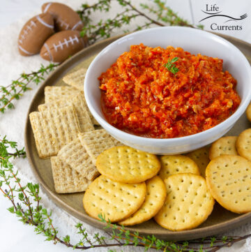 square crop of a bowl of red pepper dip with a plate full of crackers, and some fresh herbs, footballs in the background.