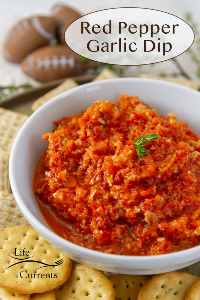 A white bowl filled with red pepper dip with crackers around it and some small footballs in the background, title on upper right: Red Pepper Garlic Dip .