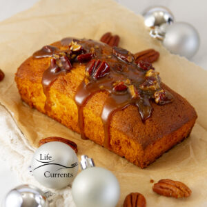 square crop of one eggnog pound cake topped with pecan caramel and surrounded by Christmas ornaments.
