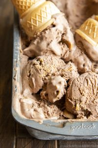 A close up of scoops of chocolate peanut butter ice cream in a metal pan, with an upside down cone on top.