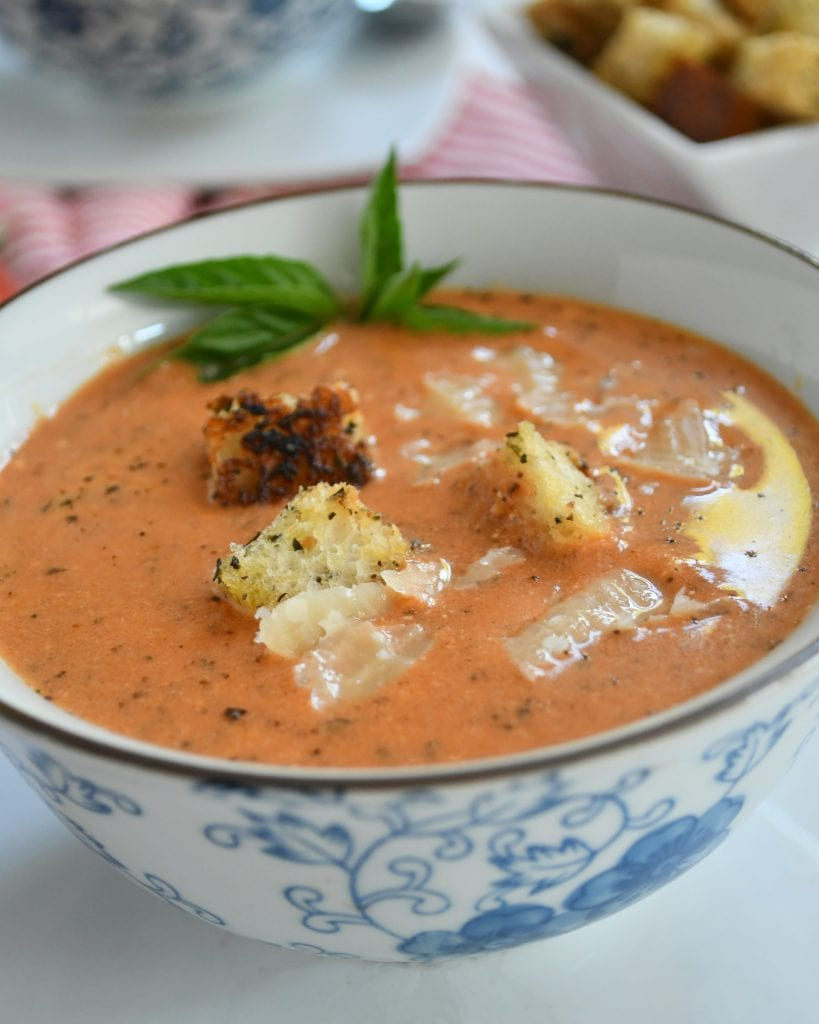 A white adn blue bowl of red tomato basil soup topped with fresh basil, croutons, and Parmesan cheese
