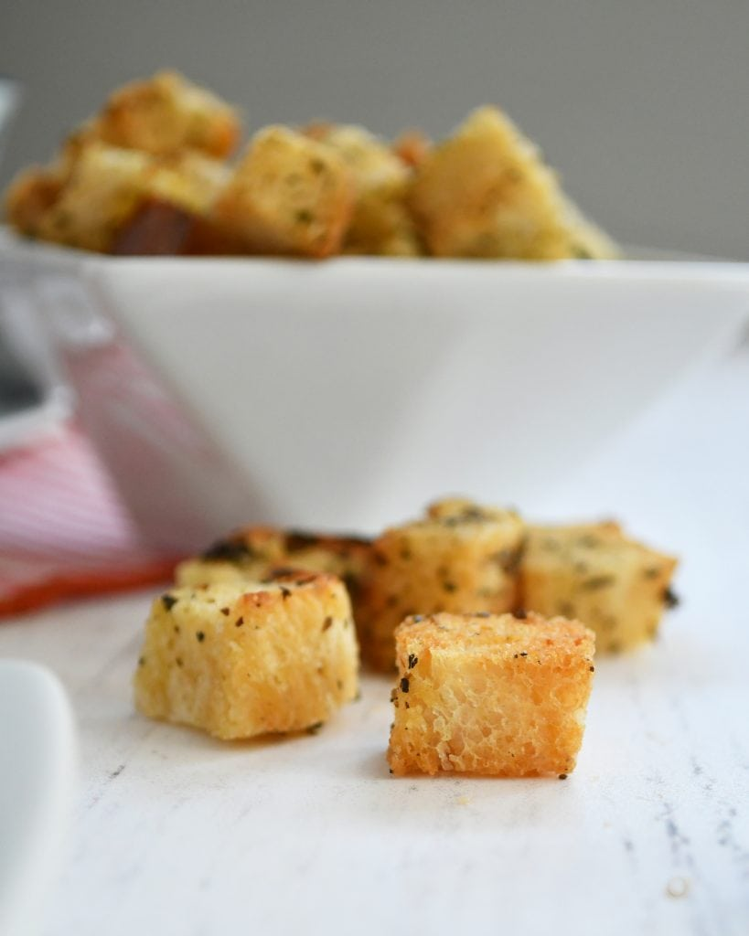 One white bowl filled with Italian seasoned croutons with 5 croutons on the outside of the bowl