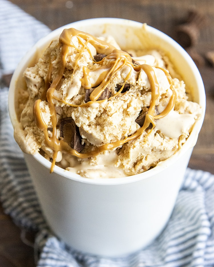 A white container full of an orange colored peanut butter ice cream, with peanut butter cups, and drizzled with peanut butter.