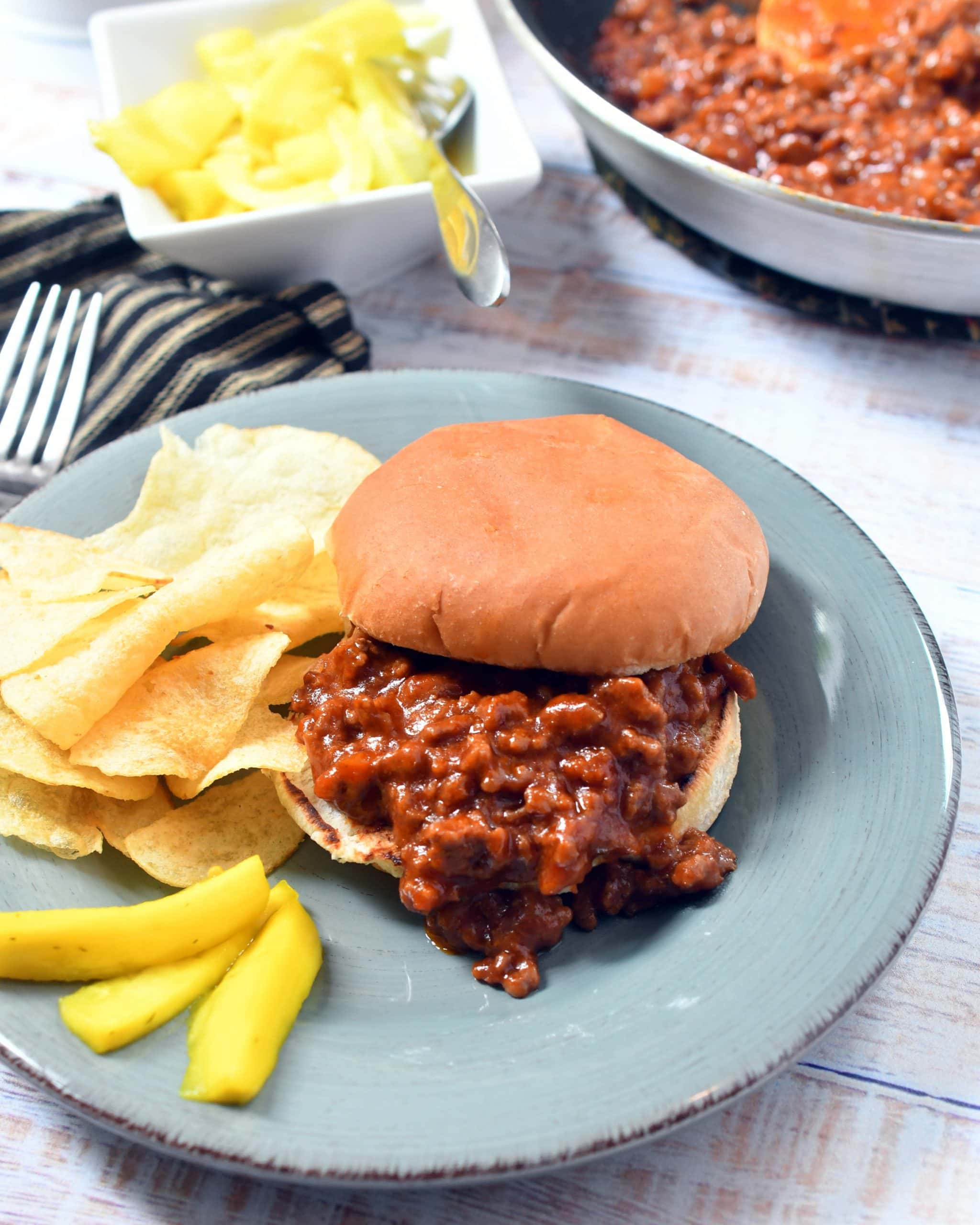 Sloppy Joe sandwich on a teal plate with a side of potato chips, pickles