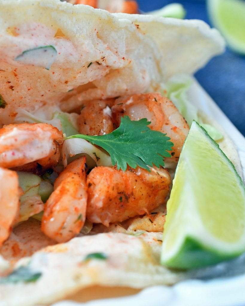 Seasoned shrimp in a corn tortilla with a lime on the side