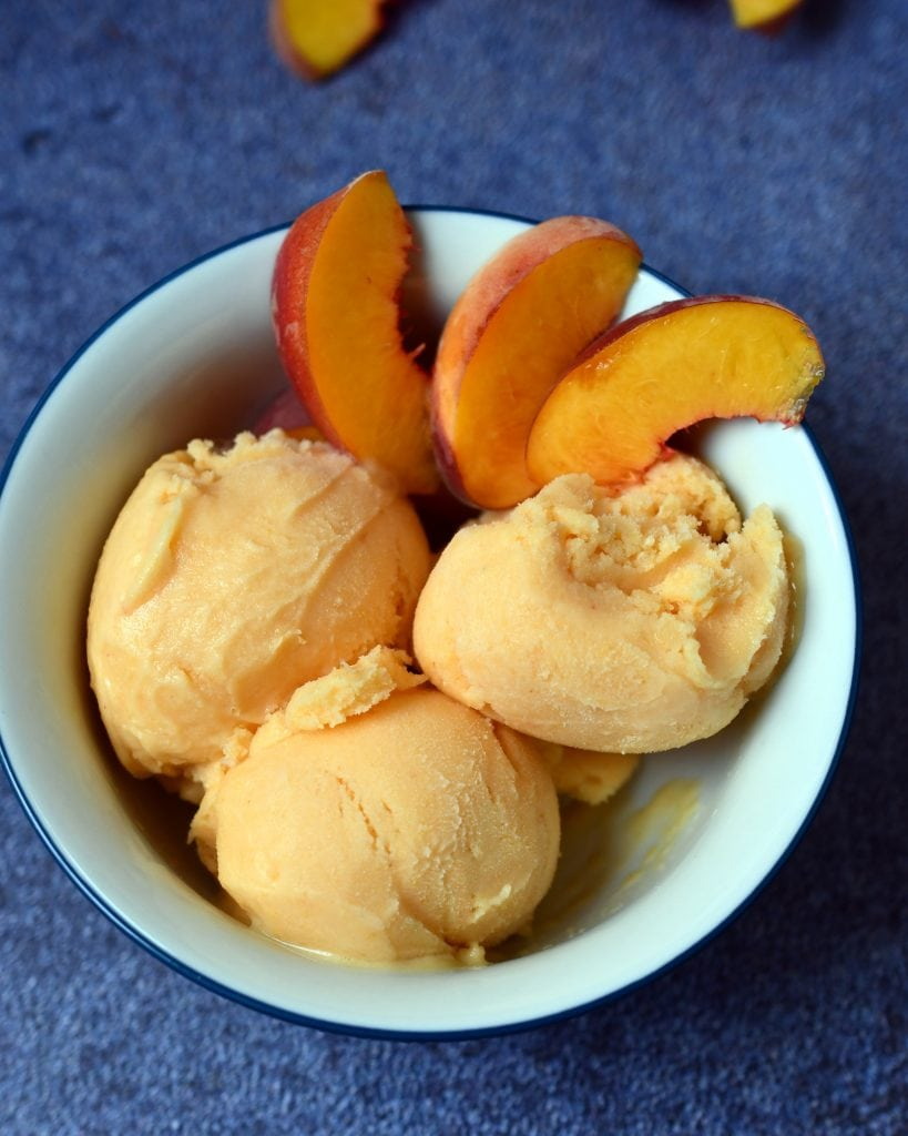 White bowl with 3 scoops of peach sherbet and 3 peach slices on blue background