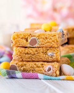 A stack of 3 blondies full of Cadbury Mini Eggs.