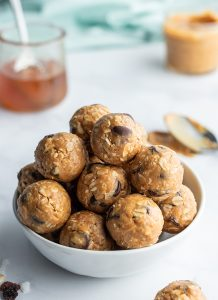 A bowl of granola balls, that are made of peanut butter, honey, oats, chocolate chips, coconut, and raisins.