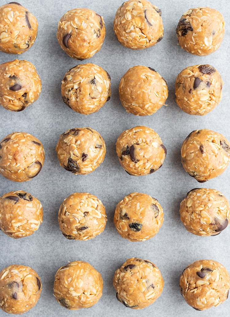 Rows of no bake granola balls on parchment paper.