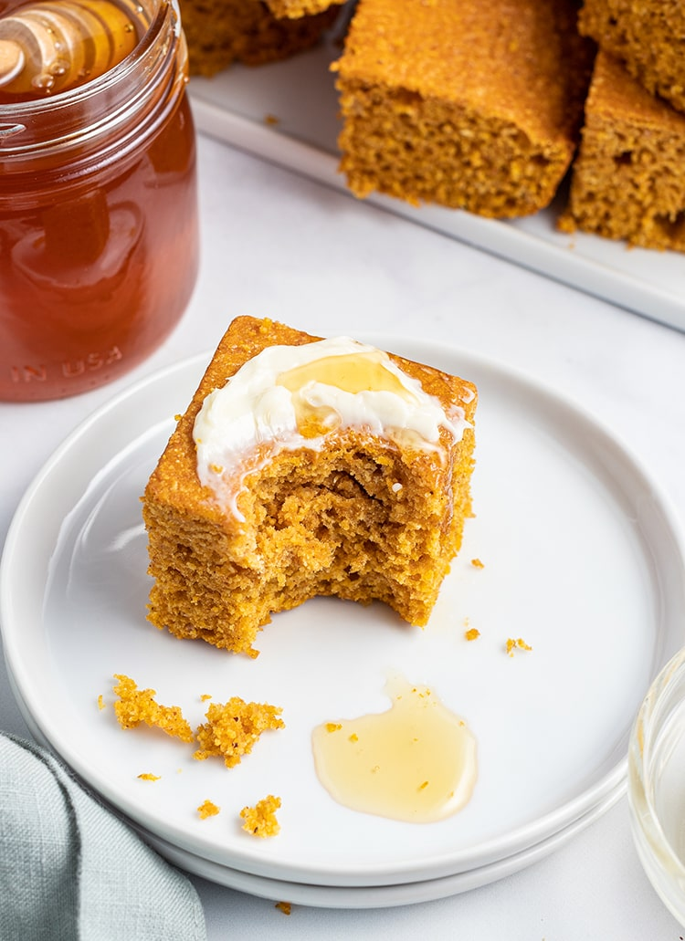 A piece of pumpkin cornbread with butter and honey on it, and a bite taken out.