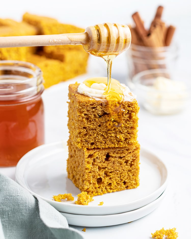 A stack of two pieces of pumpkin corn bread with butter and honey drizzled on top