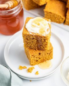 A stack of two pieces of pumpkin corn bread with butter and honey on top