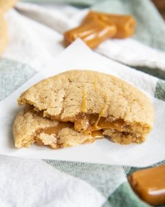 A caramel apple cider cookie broken in half and stacked on top of itself to show the caramel.
