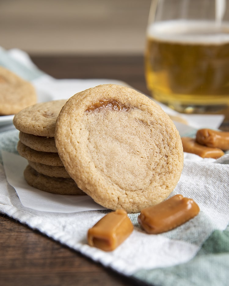 A caramel apple cider cookie leaning against a stack of cookies with two caramels on the ground in front of it.