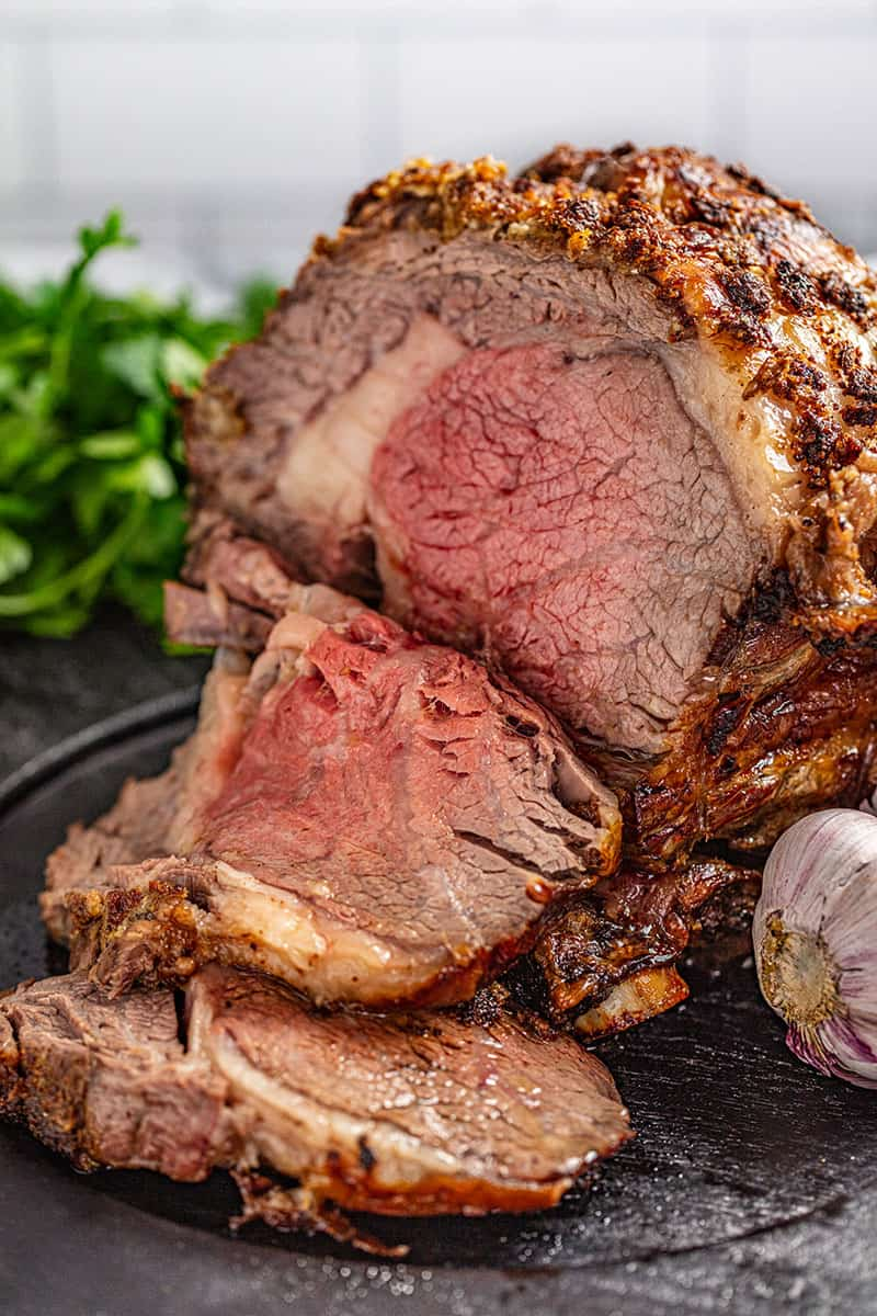 A prime rib with a golden crust and pink interior, There are a couple slices of it cut off and laying in front of the roast.