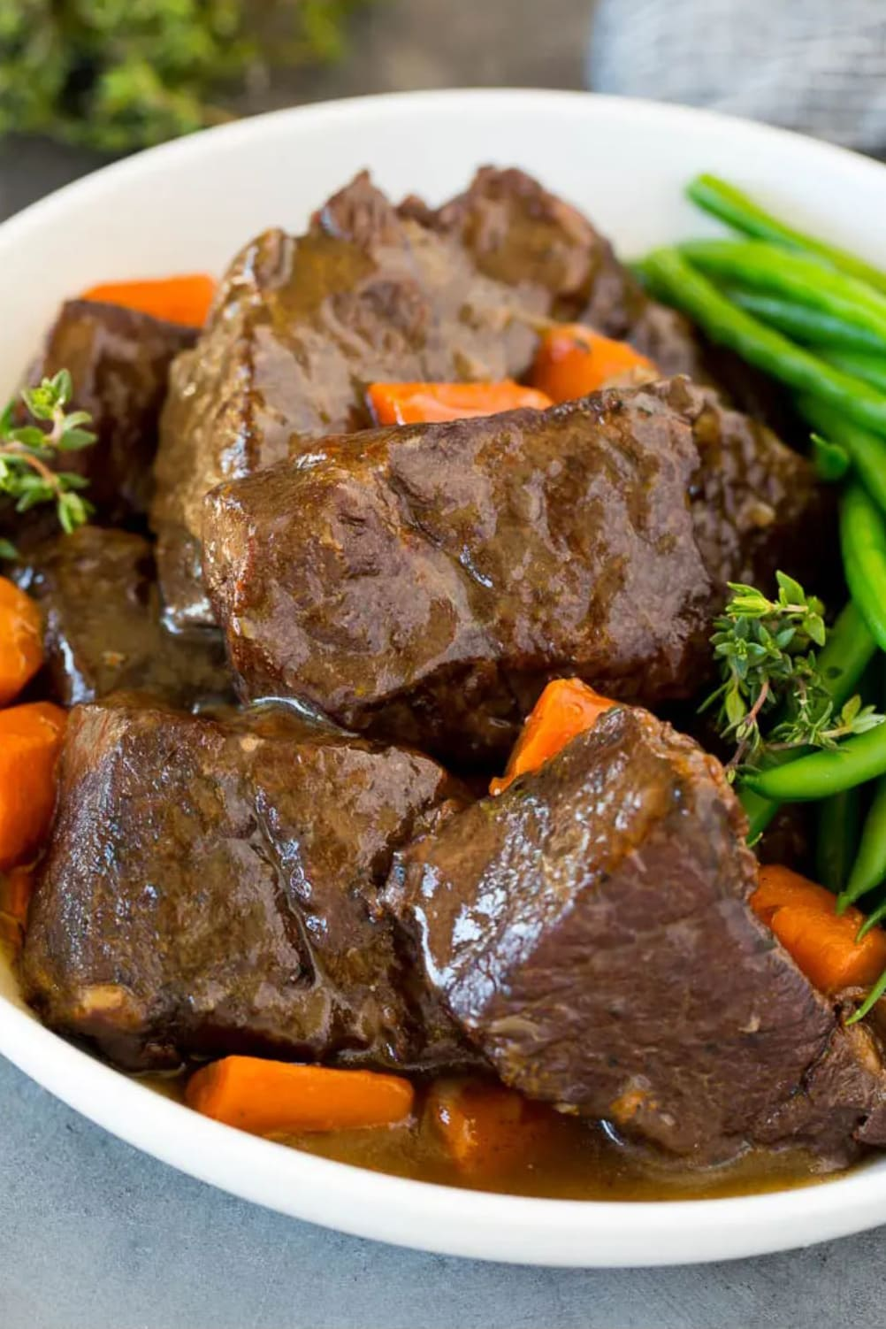 Short ribs covered in a type of gravy on a plate with carrots and green beans.