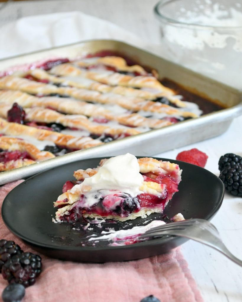 a slice of triple berry rhubarb slab pie topped with whipped topping on a brown plate with a fork, the slab pie has a piece missing, framed by the slab pie in a pan behind it