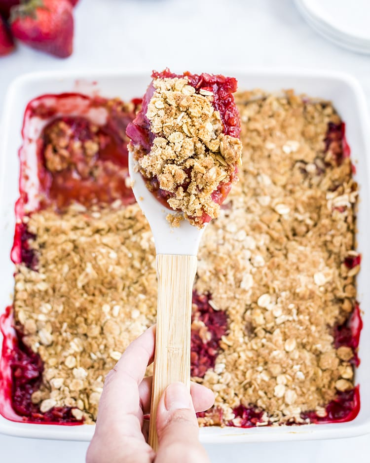 A scoop of strawberry crumble with a pan of it below.