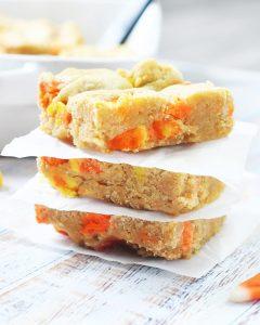 A stack of candy corn blondies with parchment paper between each one.