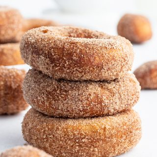 A stack of three cinnamon sugar donuts with more donuts behind them.