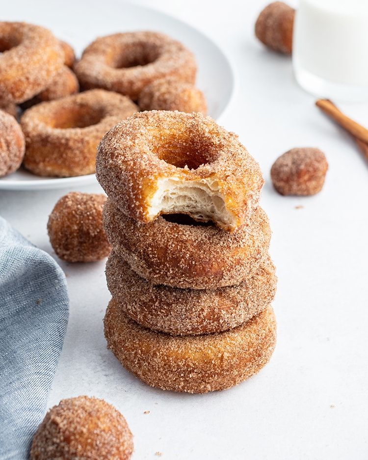 A stack of cinnamon sugar biscuit donuts, and the top donut has a bite out of it showing the middle.
