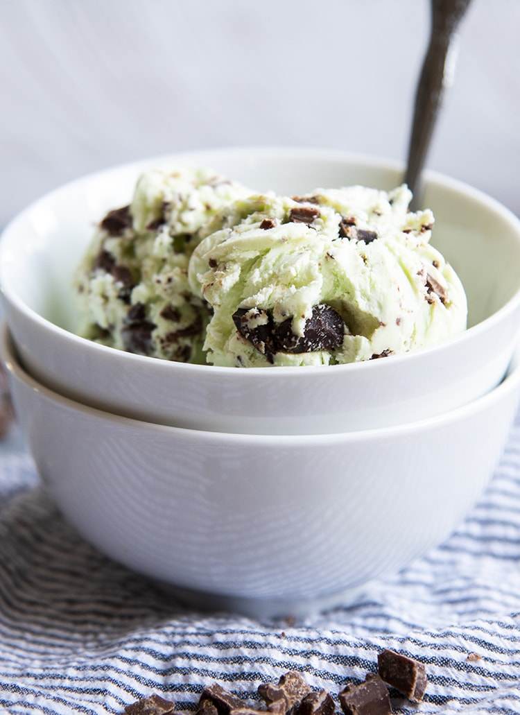 A side shot of a two white bowls stacked, and the top bowl has mint chocolate chip ice cream in it.