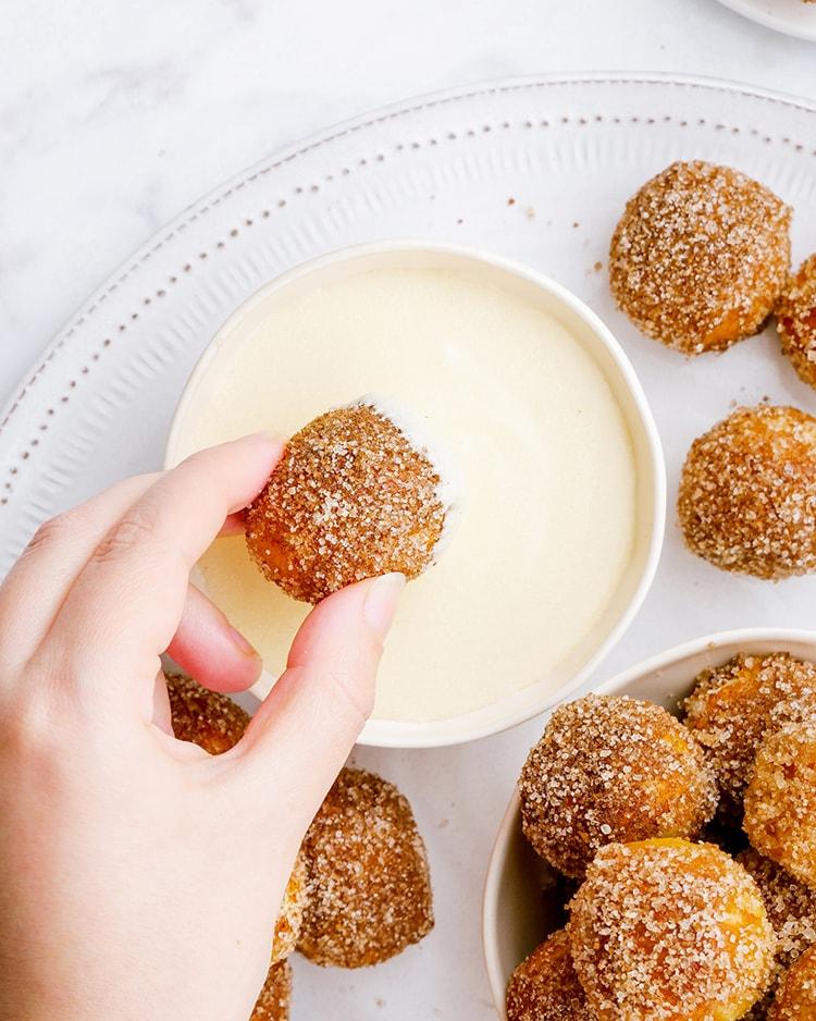 A cinnamon sugar pretzel ball being dipped into a bowl of sweet cream cheese dip.
