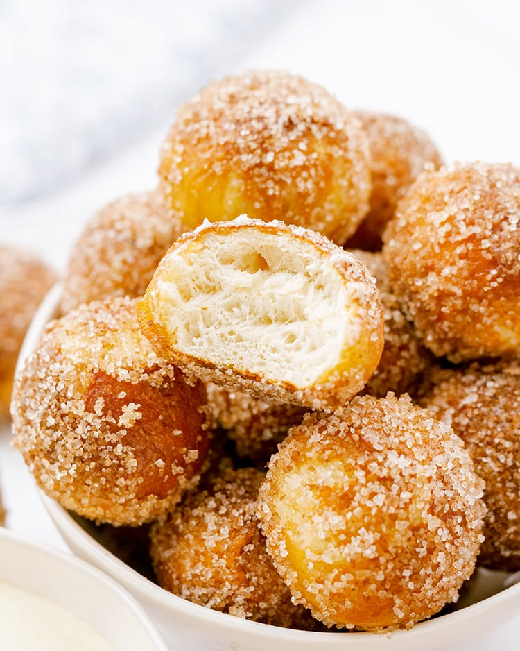 A close up of cinnamon sugar soft pretzel bites. One is bit open showing the soft bread in the middle.