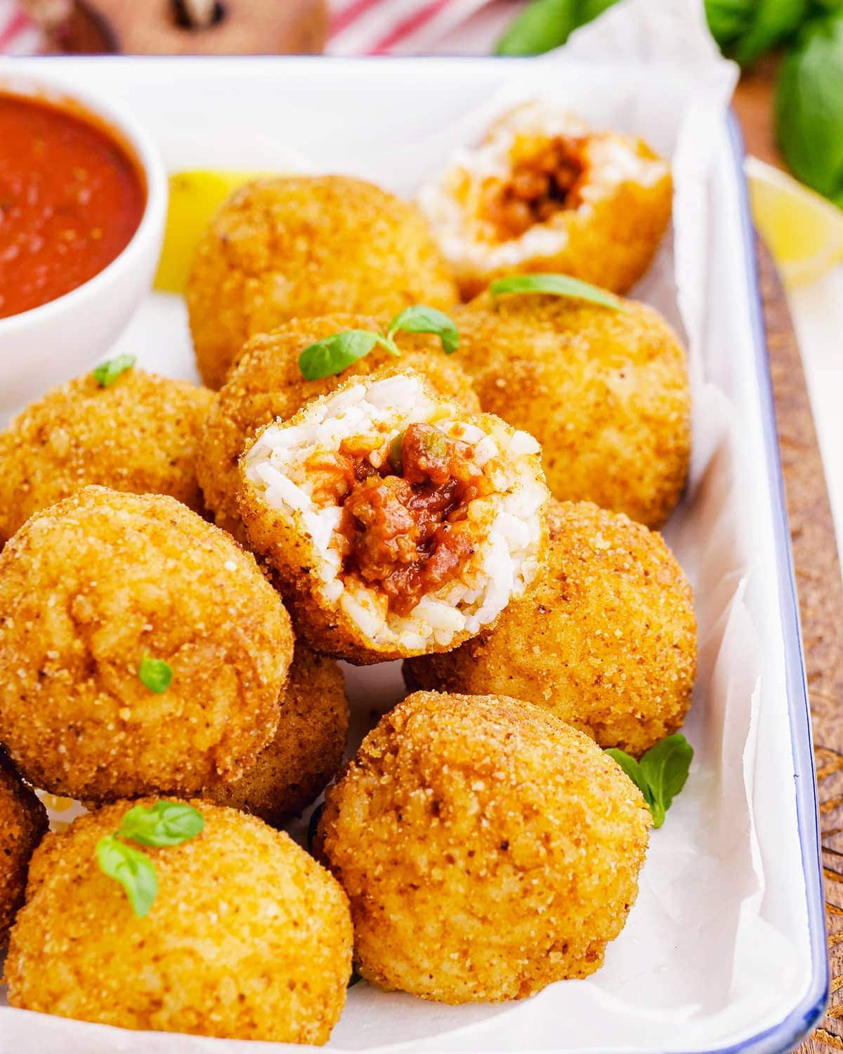 A pile of arancini rice balls, and one is bit into showing the ragu filling.