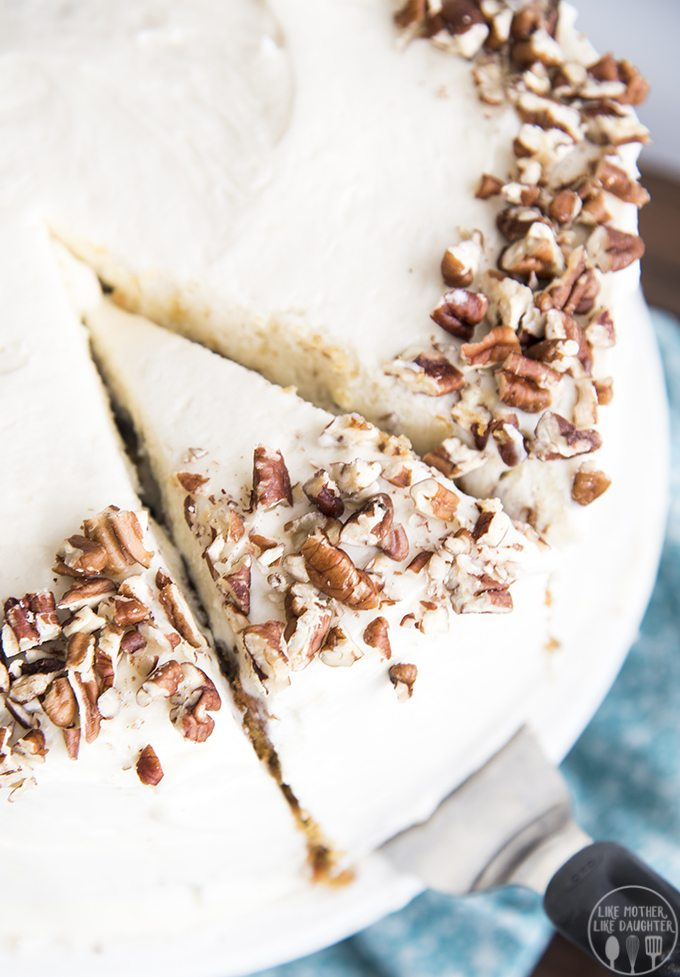 A round carrot cake that has one slice cut out and is being removed by a spatula. The cake is covered in cream cheese frosting and sprinkled with chopped nuts.