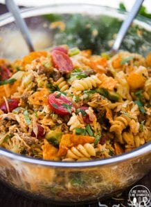 A glass bowl full of a taco pasta salad, with rotini pasta, Doritos, tomatoes, ground beef, and topped with cilantro.