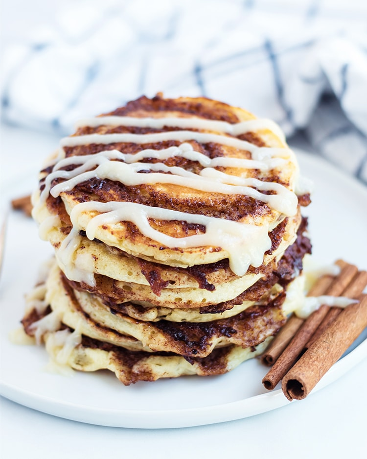 A stack of cinnamon roll pancakes drizzled with cream cheese frosting on a plate