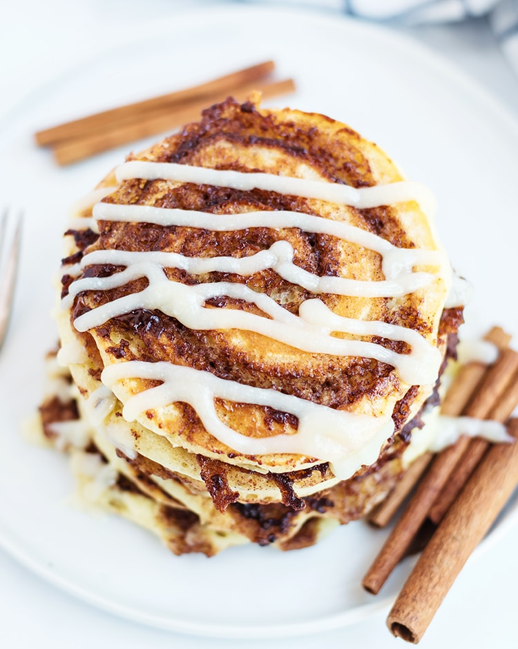 Cinnamon Roll Pancakes with a cinnamon swirl and cream cheese syrup drizzled across the top