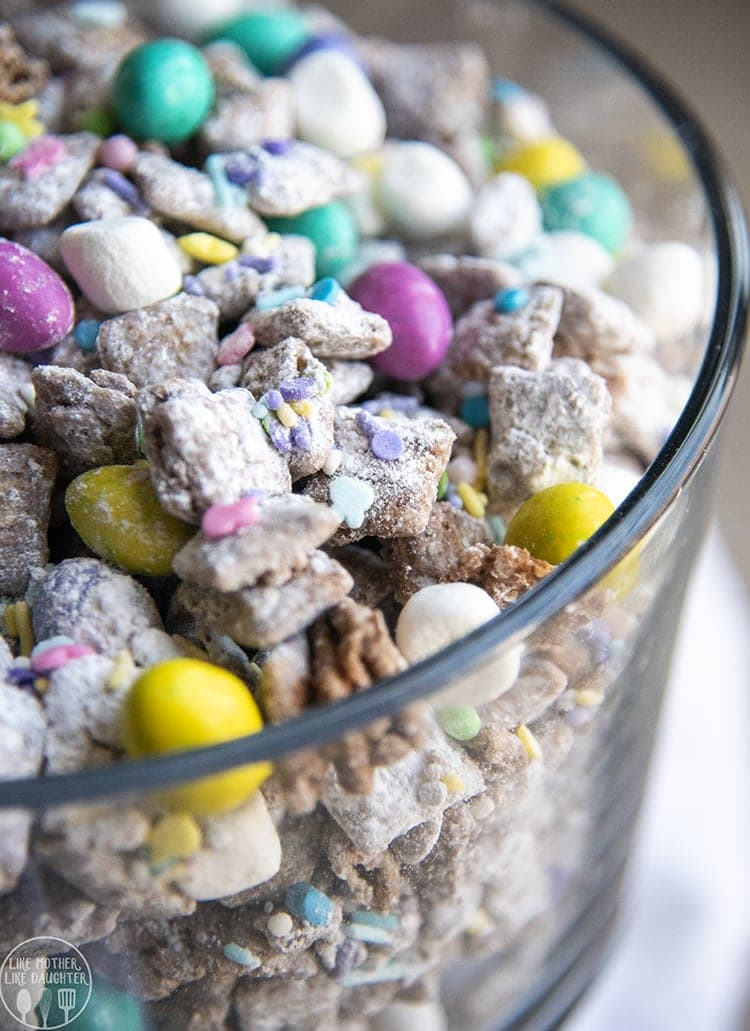 A trifle dish full of Easter muddy buddies. There are pastel colored m&ms, and sprinkles, and mini marshmallows mixed in with the chocolate coated chex.