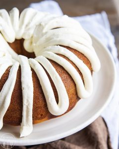 pumpkin bundt cake with cream cheese frosting on a white plate