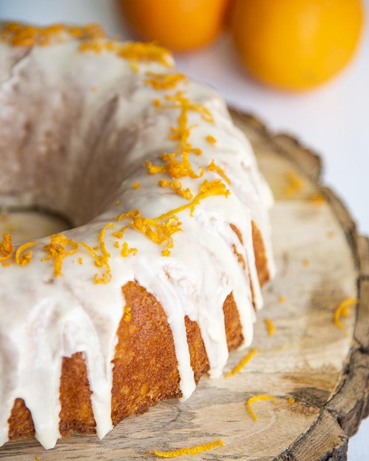 Orange Bundt Cake with glaze drizzled over the top, and orange zest