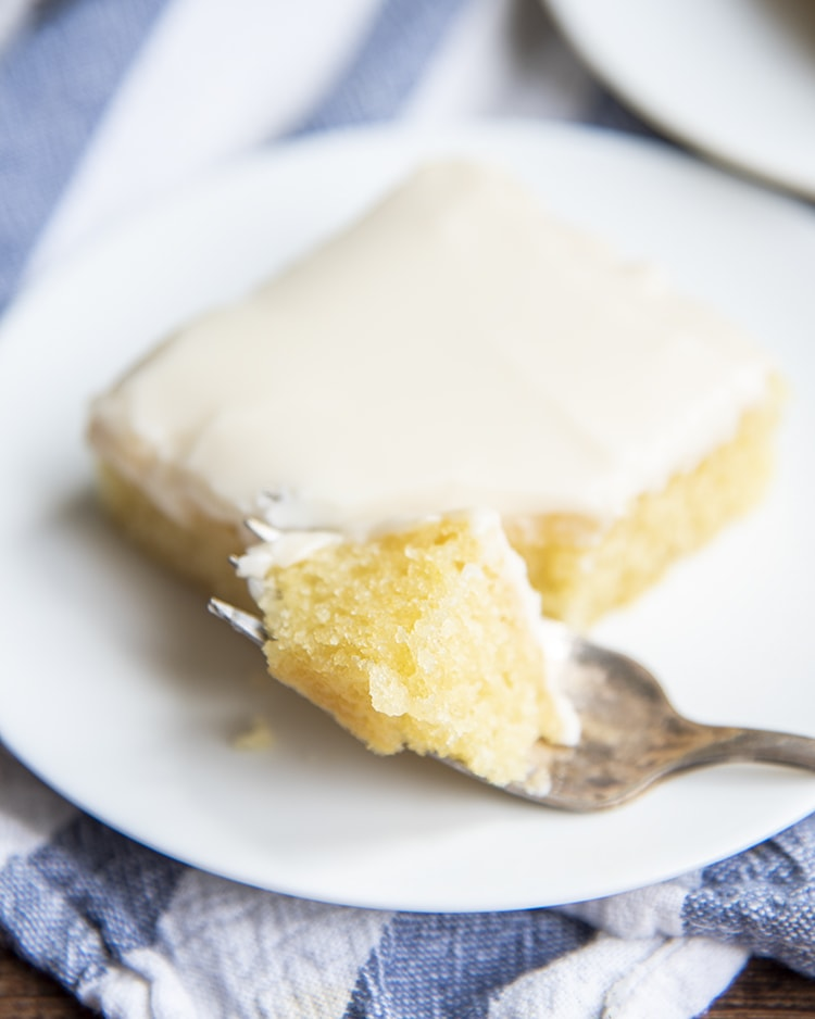 A slice of white texas sheet cake with a bite on a fork