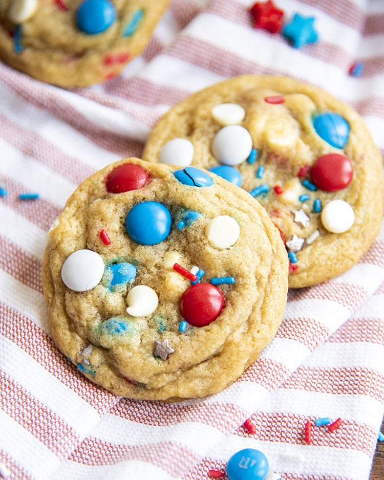 Fourth of July Cookies filled with red white and blue m&ms on a red and white cloth.