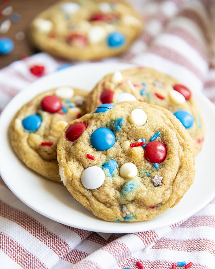 Fourth of July Cookies filled with red white and blue m&ms, white chocolate chips, and sprinkles on a white plate