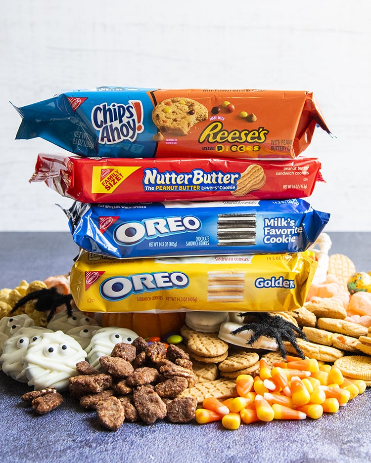 A stack of Chips Ahoy, Nutter Butters, and Oreos on top of a pile of treats.